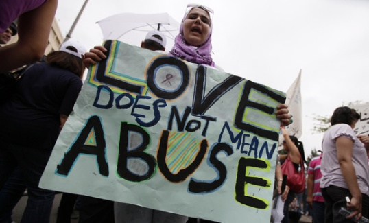 A female activist holding a placard stands amongst men during a protest against family violence near the parliament and government palace in Beirut